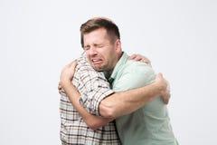 El hijo maduro está llorando en su hombro del padre y causa trastornada de sensación de su error imagen de archivo libre de regalías