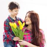 El hijo que abraza a su madre y le da las flores Foto de archivo libre de regalías