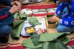 El hijo que aprende hacer que Chungkin se apelmaza por las manos con su primer del padre, torta de Chungkin es el vietnamita trad Fotografía de archivo libre de regalías