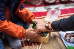 El hijo que aprende hacer que Chungkin se apelmaza por las manos con su primer del padre, torta de Chungkin es el vietnamita trad Imagen de archivo