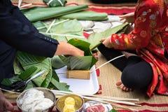 El hijo que aprende hacer que Chungkin se apelmaza por las manos con su primer del padre, torta de Chungkin es el vietnamita trad Foto de archivo