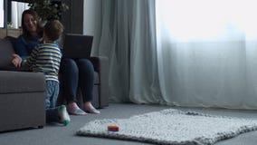 El hijo que muestra el juguete de la mamá del diseñador magnético junta las piezas almacen de metraje de vídeo