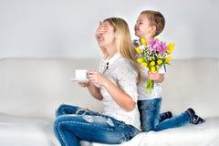 El hijo se sostiene detrás de su ramo de flores hermosas para su madre querida Fotos de archivo libres de regalías