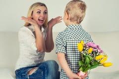 El hijo se sostiene detrás de su ramo de flores hermosas para su madre querida Foto de archivo libre de regalías