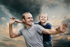 El hijo sonriente feliz con el retrato del padre en el frío entona el cielo Foto de archivo libre de regalías