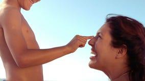 El hijo sonriente que aplica la protección solar en sus madres sospecha almacen de video