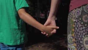 El hijo toma la mano del ` s de la madre y caminan almacen de video
