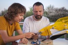 El hijo y el padre hicieron los aviones modelo radio-controlados hechos en casa ai fotografía de archivo
