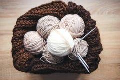 El hilado beige, las agujas que hacen punto y una bufanda marrón están en la cesta fotografía de archivo libre de regalías
