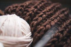 El hilado beige, las agujas que hacen punto y una bufanda marrón están en la cesta fotografía de archivo