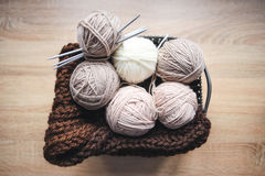 El hilado beige, las agujas que hacen punto y una bufanda marrón están en la cesta imagenes de archivo