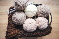 El hilado beige, las agujas que hacen punto y una bufanda marrón están en la cesta fotos de archivo libres de regalías