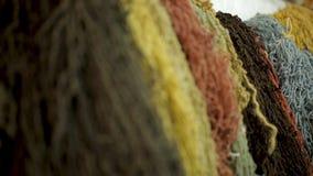 El hilado colorido de las lanas de las ovejas para la alfombra que teje, fabrica la materia textil industrial almacen de video