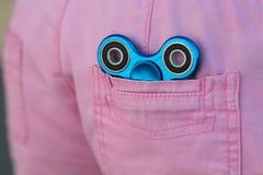 El hilandero popular de la persona agitada del metal azul en el bolsillo trasero de vaqueros rosados, de juguete del alivio de la Fotos de archivo
