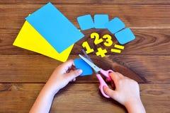 El hild del ¡de Ð sostiene las tijeras y corta la tarjeta de papel figuras de papel Foto de archivo