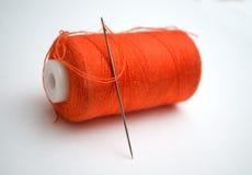 El hilo anaranjado con una aguja Imágenes de archivo libres de regalías