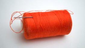 El hilo anaranjado con una aguja Fotografía de archivo libre de regalías