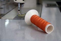 El hilo anaranjado en el rollo del hilo pasó horizontal en la máquina de coser, con el uso ya de la ropa de costura Imágenes de archivo libres de regalías