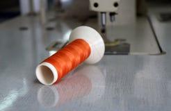 El hilo anaranjado en el rollo del hilo puso horizontal en la máquina de coser Fotos de archivo libres de regalías