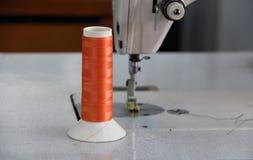 El hilo anaranjado en el rollo del hilo puso vertical en la máquina de coser Imagenes de archivo
