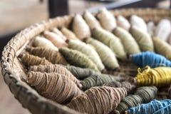 El hilo del algodón rueda en la cesta de trilla Foto de archivo