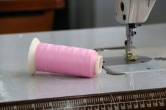 El hilo rosado en el rollo del hilo pasó horizontal en la máquina de coser, con el uso ya de la ropa de costura Imagenes de archivo