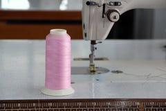 El hilo rosado en el rollo del hilo pasó vertical en la máquina de coser, con el uso ya de la ropa de costura Foto de archivo libre de regalías