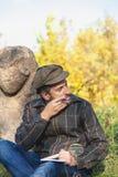 El historiador docto se sienta antes de la escultura de piedra en el montón Imagen de archivo libre de regalías