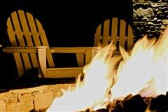 El hogar Adirondack preside el hoyo del fuego foto de archivo