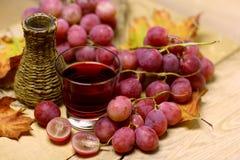 El hogar hizo los vinos la botella y las uvas de mimbre Foto de archivo