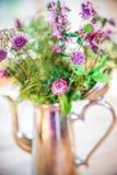 El hogar hizo el ramo fresco de las flores salvajes en el pote de plata en la tabla de madera imágenes de archivo libres de regalías