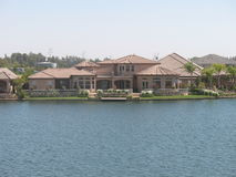 El hogar rosado del estuco con el tejado de teja rosado atraviesa orilla del lago Fotografía de archivo libre de regalías
