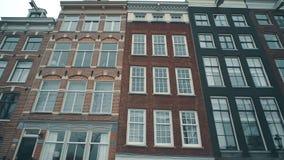 El holandés típico contiene fachadas a lo largo de la calle en Amsterdam, Países Bajos metrajes