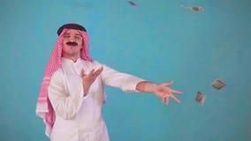 El hombre árabe alegre con un bigote y una ropa tradicional con Audi, lanza el dinero almacen de metraje de vídeo