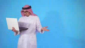 El hombre árabe decepcionado con el ordenador portátil a disposición se coloca en fondo azul almacen de video