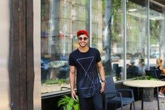 El hombre árabe del individuo confiado hermoso sostiene el teléfono elegante, sonrisas y el po Imagen de archivo