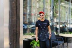 El hombre árabe del individuo confiado hermoso sostiene el teléfono elegante, sonrisas y el po Fotos de archivo