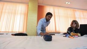 El hombre árabe en camisa azul pinta cuidadosamente el proyecto en la hoja de papel metrajes