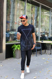 El hombre árabe joven feliz va en el camino, sonríe y utiliza el teléfono, mana Imagenes de archivo