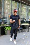 El hombre árabe joven feliz va en el camino, sonríe y utiliza el teléfono, mana Imagen de archivo libre de regalías