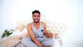 El hombre árabe joven se relaja y sonríe mientras que miente en cama en dormitorio brillante metrajes