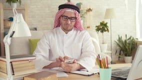 El hombre árabe que se sienta en la tabla y él utiliza un smartphone almacen de video