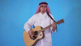El hombre árabe toca torpe la guitarra acústica en fondo azul almacen de metraje de vídeo