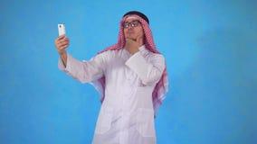 El hombre árabe toma un selfie en la cámara del smartphone en un fondo azul metrajes