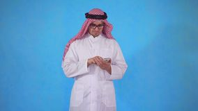 El hombre árabe utiliza un smartphone en fondo azul metrajes