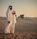 El hombre árabe y un adolescente en el desierto y miran la puesta del sol fotos de archivo libres de regalías