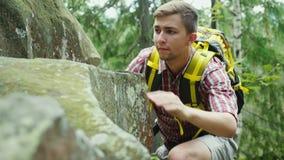 El hombre útil con una mochila sube en una roca Concepto - la búsqueda de una meta almacen de video