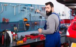 El hombre 30-35 años es listo para utilizar sus herramientas Foto de archivo