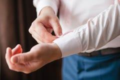 El hombre abotona la mancuerna en la camisa de las mangas de los puños Fotos de archivo libres de regalías