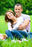 El hombre abraza a la muchacha que se sienta en hierba en parque Fotos de archivo libres de regalías